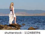 Girl Stands On A Rock And...