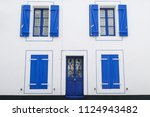 white facade house with blue... | Shutterstock . vector #1124943482