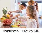 Stock photo girl and other kids at the fruit buffet at the cafeteria in elementary school 1124992838