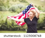 woman holding american flag in... | Shutterstock . vector #1125008768