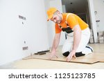 worker joining parquet floor. | Shutterstock . vector #1125123785