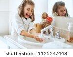 cute little girl is washing... | Shutterstock . vector #1125247448