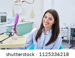 a woman is sitting in a dental... | Shutterstock . vector #1125336218