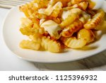 canadian poutine crinkle cut... | Shutterstock . vector #1125396932