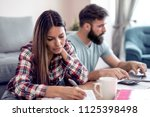 serious young couple paying... | Shutterstock . vector #1125398498
