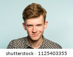 Small photo of smug smile. man with a self satisfied smirk. portrait of a young guy on light background. emotion facial expression. feelings and people reaction.