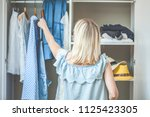 girl near a wardrobe with... | Shutterstock . vector #1125423305