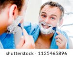 a handsome man shaves his beard ... | Shutterstock . vector #1125465896