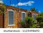 louvered windows in old stone... | Shutterstock . vector #1125498692