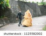 bridegroom helps walking bride... | Shutterstock . vector #1125582002