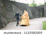 bridegroom helps walking bride... | Shutterstock . vector #1125582005