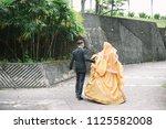 bridegroom helps walking bride... | Shutterstock . vector #1125582008