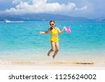 child playing on tropical beach....   Shutterstock . vector #1125624002