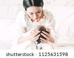 mother holding baby in her arms ... | Shutterstock . vector #1125631598