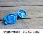 blue sun glasses on natural... | Shutterstock . vector #1125673382