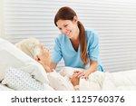 caring geriatric nurse cares... | Shutterstock . vector #1125760376