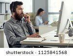 bearded man at working desk in... | Shutterstock . vector #1125841568