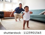 baby daughter dancing with... | Shutterstock . vector #1125901565