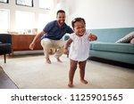 baby daughter dancing with... | Shutterstock . vector #1125901565