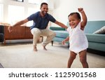 baby daughter dancing with... | Shutterstock . vector #1125901568