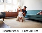 Small photo of Father Encouraging Baby Daughter To Take First Steps At Home