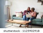 senior couple sitting on sofa... | Shutterstock . vector #1125902918