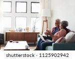 senior couple sitting on sofa... | Shutterstock . vector #1125902942