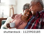 loving senior couple sitting on ... | Shutterstock . vector #1125903185