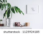 Stock photo interior of white home space with mock up poster frame tropical leaf and vintage camera 1125924185