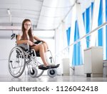 a young girl in a wheelchair is ... | Shutterstock . vector #1126042418
