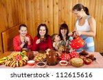Women drinks tea with pancakes during  Pancake Week in Russia - stock photo