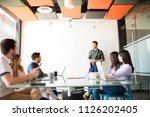 young hispanic man giving a... | Shutterstock . vector #1126202405