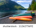 row of colorful kayaks lying on ... | Shutterstock . vector #1126275692