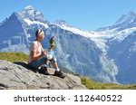 Girl holding a jug of milk and flowers against Swiss Alps - stock photo