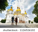 Young tourist couple in silhouette looking at Church with golden domes at Kiev Pechersk Lavra Christian complex. Old historical architecture in Kiev, Ukraine