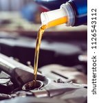 motor oil pouring to car engine. | Shutterstock . vector #1126543112