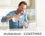 middle age man drinking a glass ... | Shutterstock . vector #1126574465