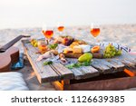 picnic on the beach at sunset...   Shutterstock . vector #1126639385