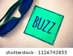 Small photo of Word writing text Buzz. Business concept for Hum Murmur Drone Fizz Ring Sibilation Whir Alarm Beep Chime Green paper beige background sunglasses ideas messages feelings thoughts.