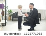 smiling father fastening... | Shutterstock . vector #1126771088