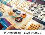 customer choosing donuts from... | Shutterstock . vector #1126793528