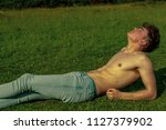 Young shirtless male adult laying in the sunshine on a warm summer's day - stock photo