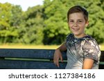 Pre-teen boy sitting outside on a warm summer's day - stock photo