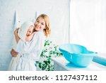 happy mother in bathrobe... | Shutterstock . vector #1127437112