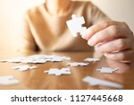 Stock photo elderly female hands trying to connect pieces of white jigsaw puzzle on wooden table creative idea 1127445668