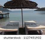 sunbed and sunshade near sea | Shutterstock . vector #1127451932