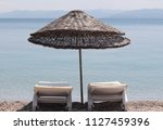 sunbed and sunshade on the... | Shutterstock . vector #1127459396