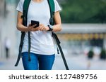 young woman walking with smart... | Shutterstock . vector #1127489756