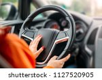 young woman driver driving a... | Shutterstock . vector #1127520905