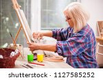 elderly woman is painting in... | Shutterstock . vector #1127585252